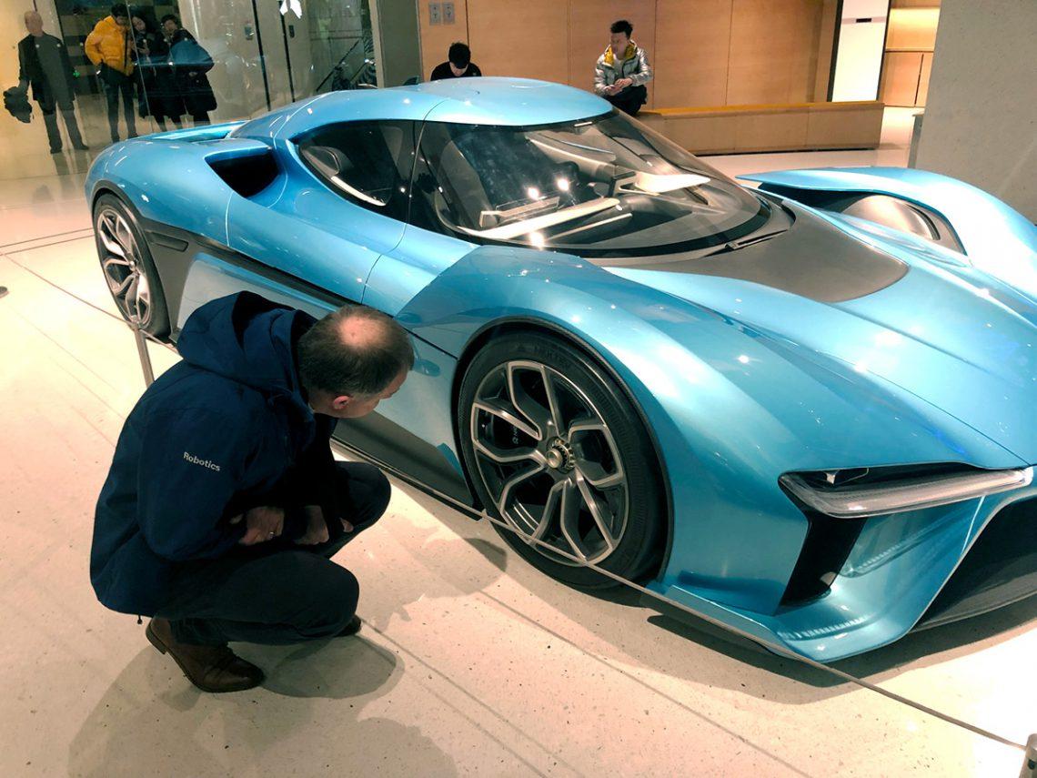 Früher haben wir diese Pose häufig auf der IAA gesehen. Heute werfen auch deutsche Ingenieure einen prüfenden Blick auf die chinesischen Autos: hier ein Elektro-Renner von NIO.