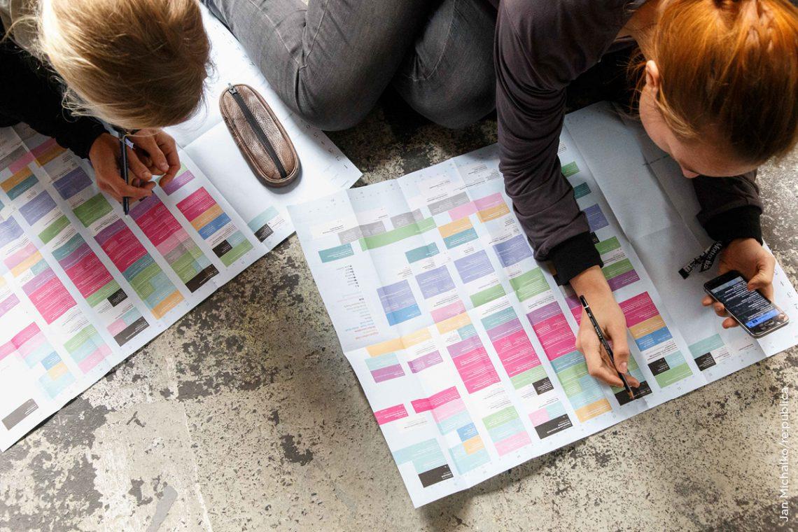 Menschen studieren das Programm auf der Digitalkonferenz re:publica in Berlin.