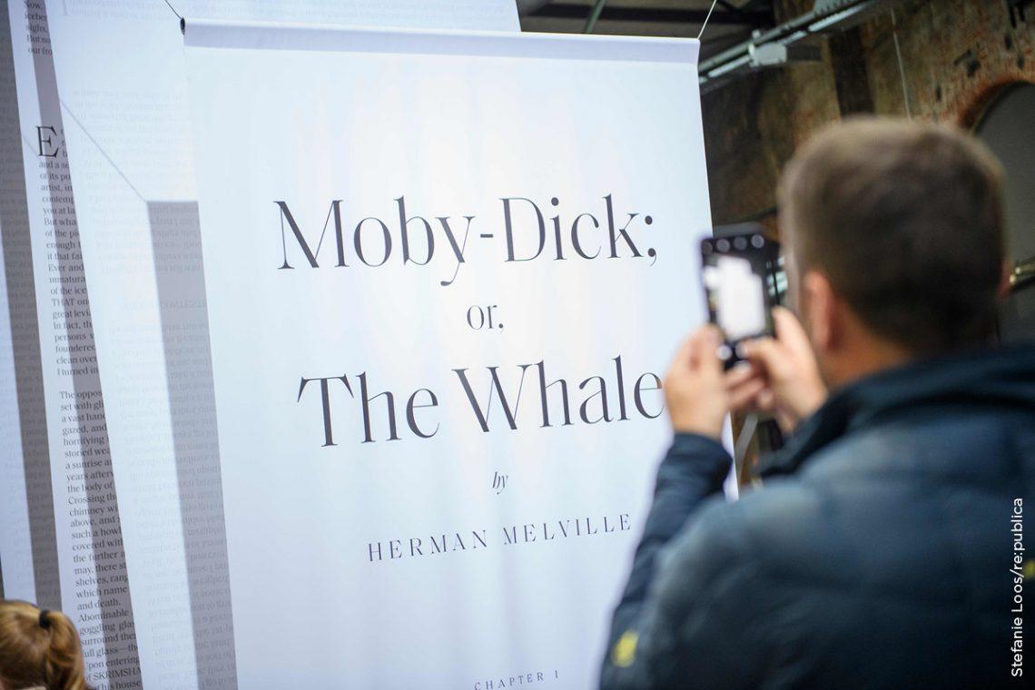 Titelseite des Romans Moby Dick, der sich auf einer langen Papierrolle durch das Gelände der Station Berlin zog, als ein Beispiel für das Motto too long; didn't read.