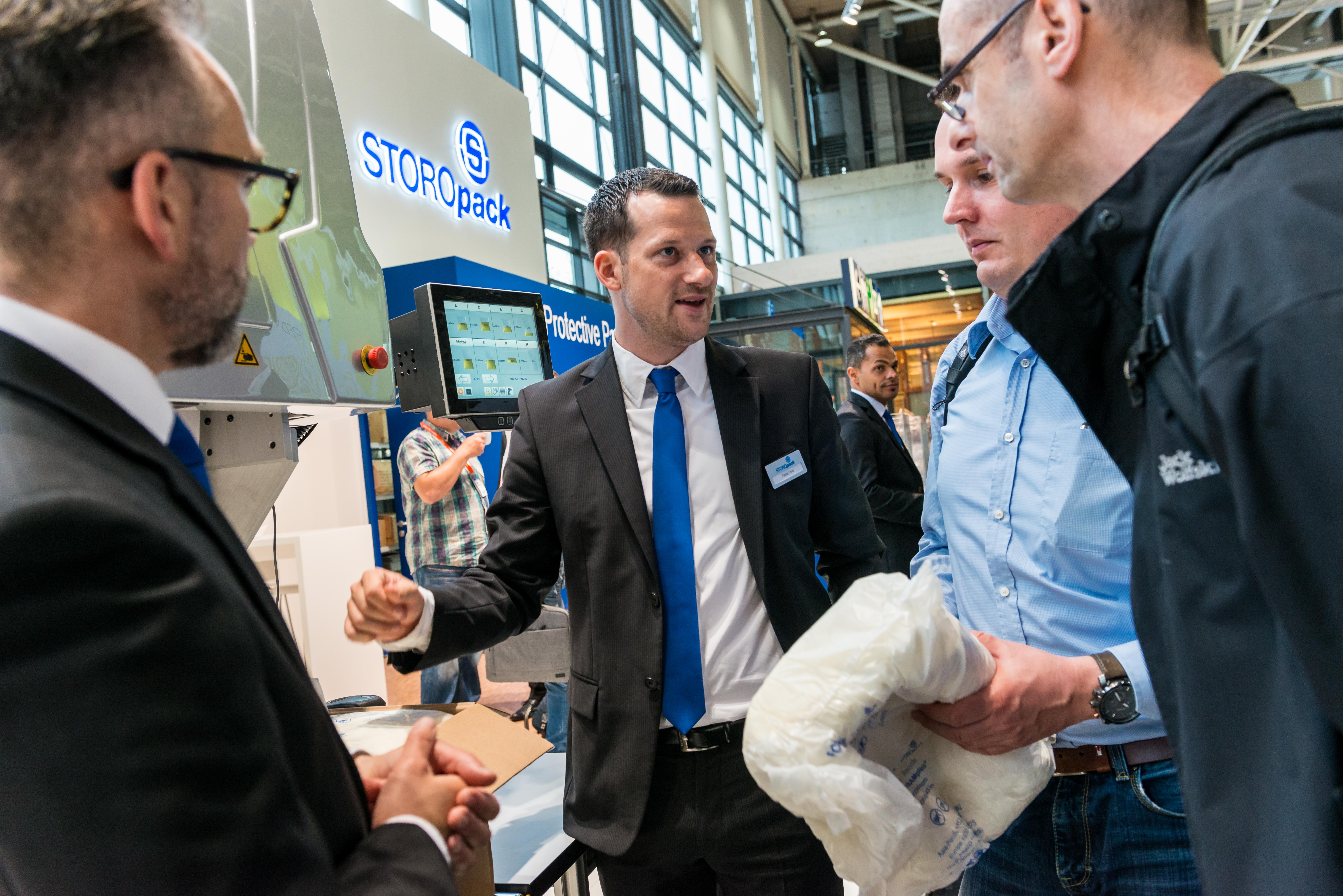 Tobias Thiel, Sales Representative FOAMplus® bei Storopack, veranschaulicht interessierten Messebesuchern die Vorteile des leistungsstarken FOAMplus® Bag Packer². Bild: Storopack